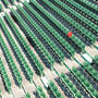 rows of green baseball stadium seats with one lone red chair