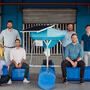 MIT Sloan students and bioFeeder co-founders posed around one of their shrimp-feeding systems.