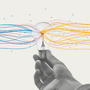 hand holding a lightbulb streaming colored lines representing data analytics