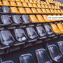 Photograph of empty stadium seats. One seat has a face mask on it.